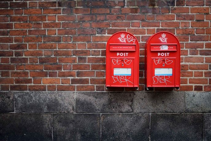 Two red mail boxes against a brick wall in the UK
